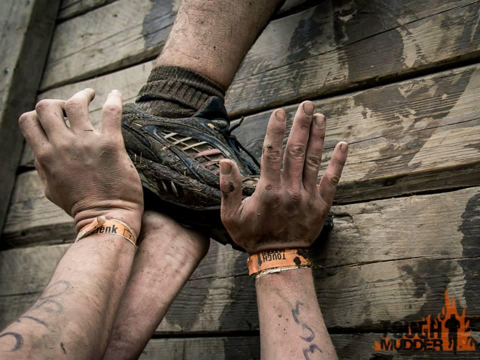 drei Hände, die einen Fuss stützen vor Holzwand