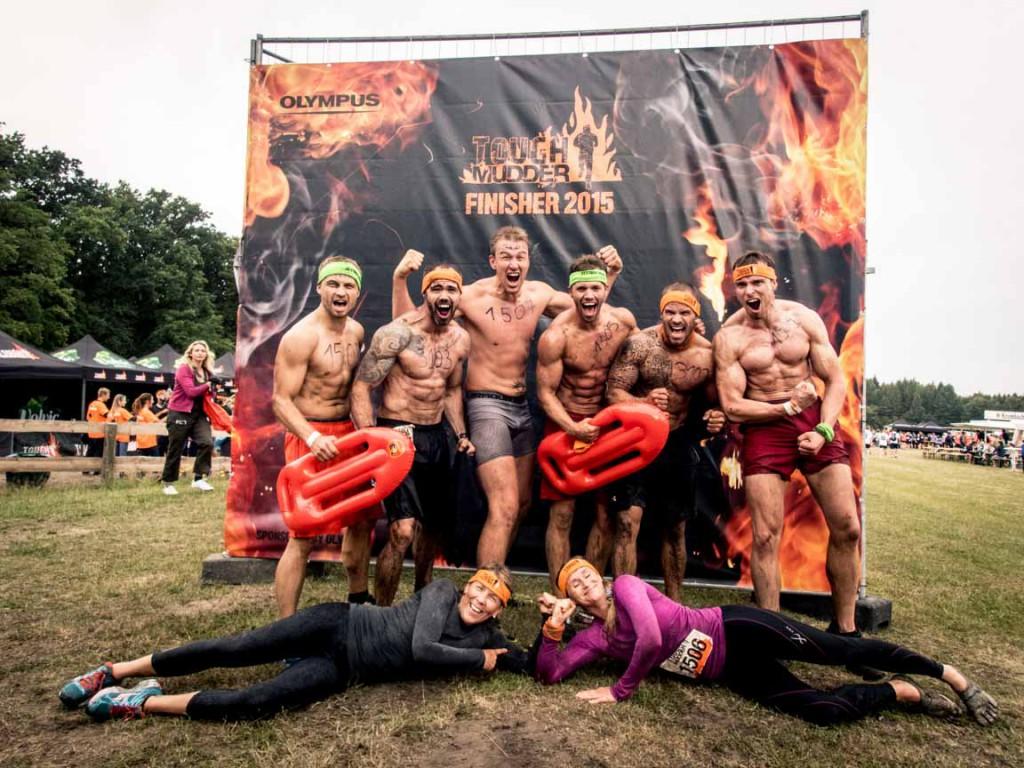 Muskulöse Männer mit freiem Oberkörper vor dem Finisher Plakat, davor zwei Frauen liegend