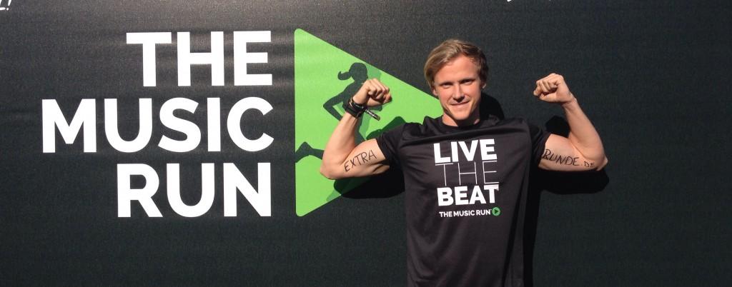 """Strphan posiert vor dem Eventlogo mit """"Extrarunde"""" Schriftzug auf seinen Bizeps"""