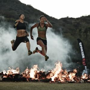 Zwei Frauen über Feuerwand springend